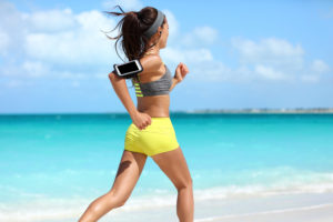 Woman running on the beach using an exercise tracker.
